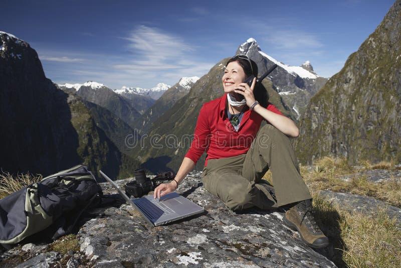 Mujer que usa el ordenador portátil y el Walkietalkie contra las montañas imagenes de archivo