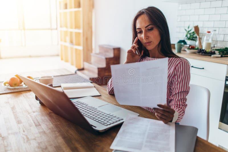 Mujer que usa el ordenador portátil y hablando en el teléfono móvil en cocina fotografía de archivo libre de regalías