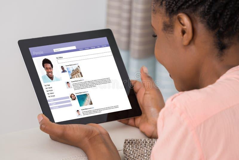 Mujer que usa el sitio social del establecimiento de una red imagenes de archivo