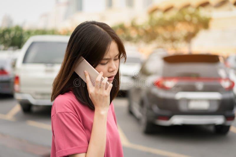 Mujer que usa el smartphone para el uso en fondo de la falta de definición del coche foto de archivo