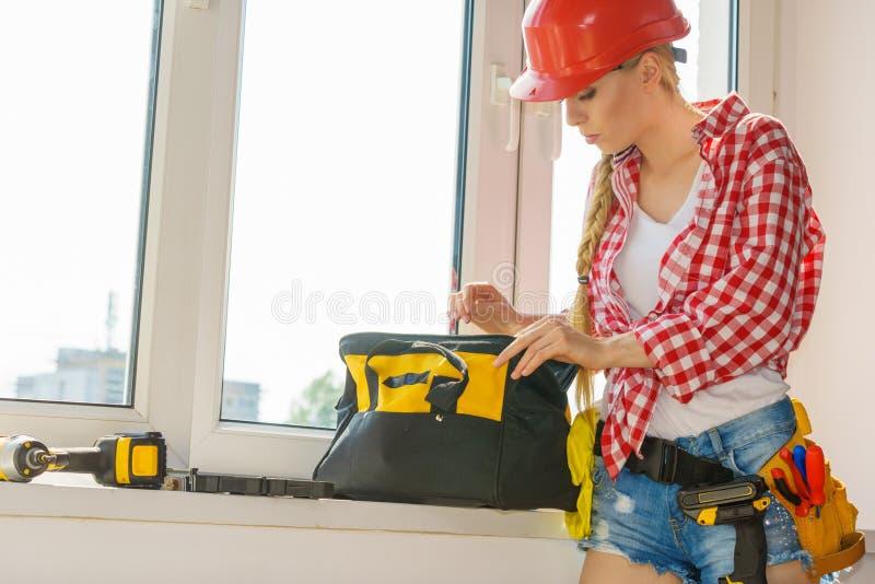 Mujer que usa el taladro para fijar o instalando ventanas fotografía de archivo