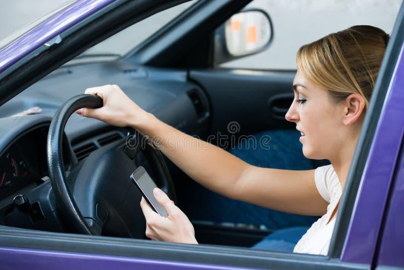 Mujer que usa el teléfono celular mientras que conduce el coche imagen de archivo libre de regalías