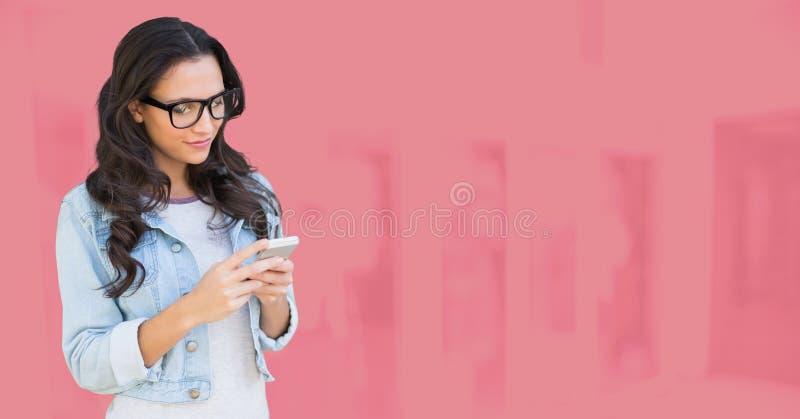 Mujer que usa el teléfono con el fondo rosado fotos de archivo