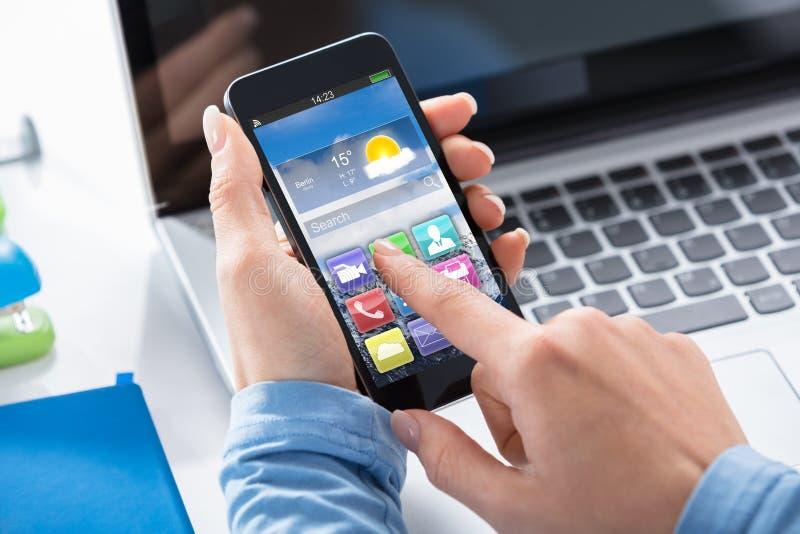 Mujer que usa el teléfono elegante con usos en la pantalla imagen de archivo