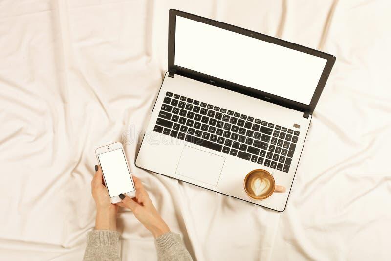 Mujer que usa el teléfono elegante en su cama Mujer que trabaja en el ordenador portátil y el café del capuchino de la bebida en  fotografía de archivo libre de regalías