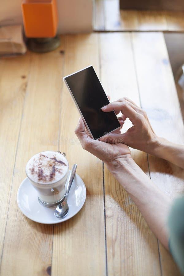 Mujer que usa el teléfono en blanco en café imagen de archivo