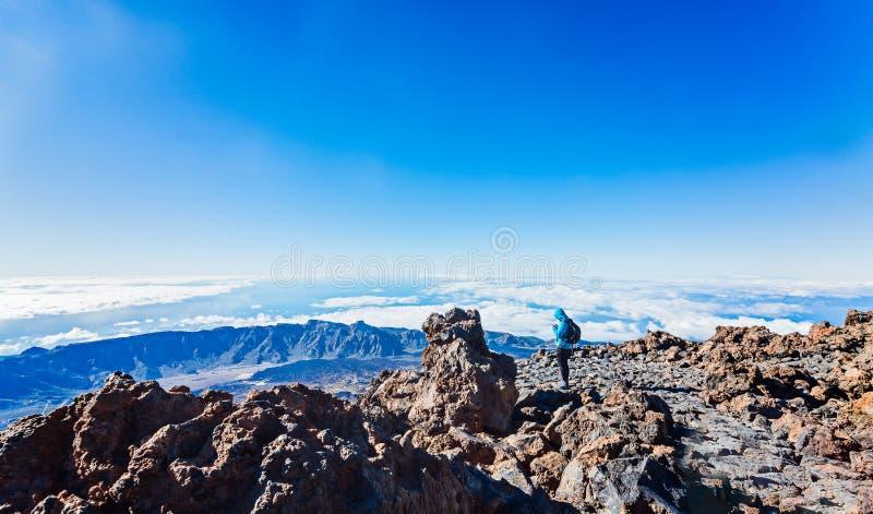 Mujer que usa el teléfono en el top del volcán de Teide fotografía de archivo