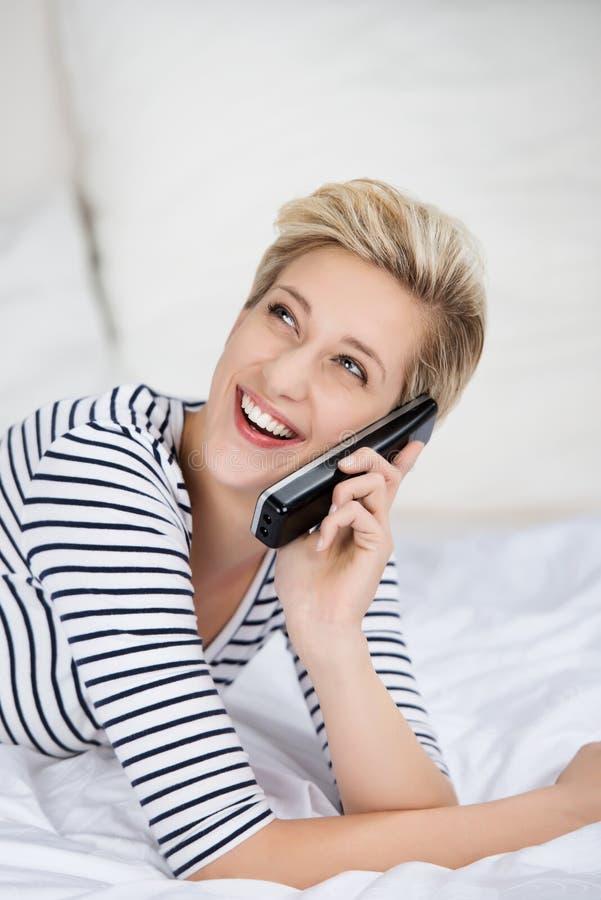 Mujer que usa el teléfono inalámbrico mientras que mira para arriba en cama foto de archivo libre de regalías