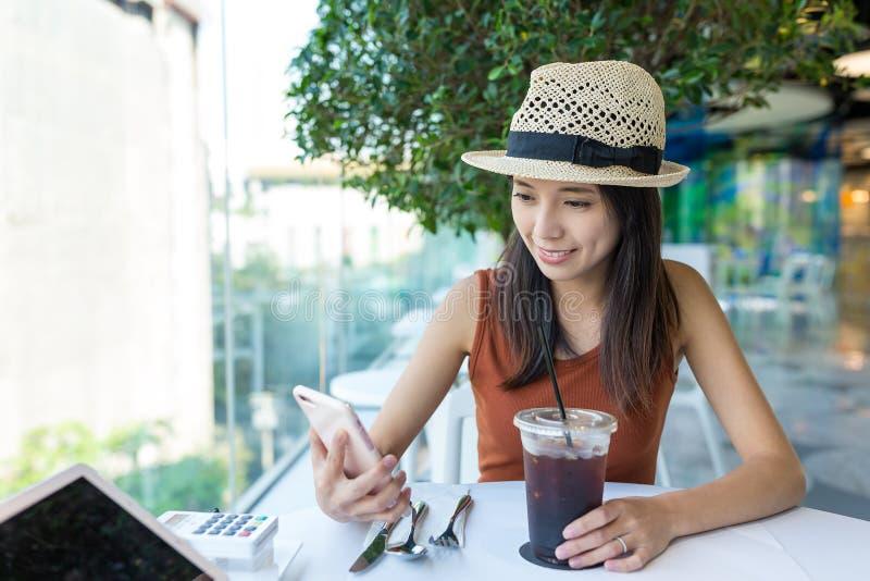 Mujer que usa el teléfono móvil en cafetería fotos de archivo
