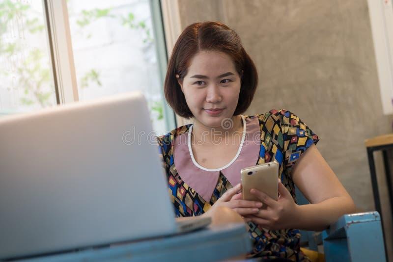 Mujer que usa el teléfono móvil en casa fotografía de archivo libre de regalías