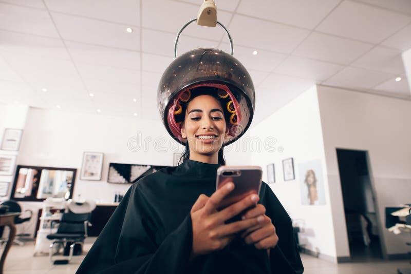 Mujer que usa el teléfono móvil en el balneario de la belleza imagen de archivo
