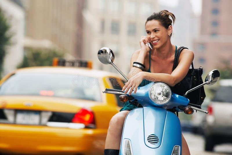 Mujer que usa el teléfono móvil en el ciclomotor imagenes de archivo