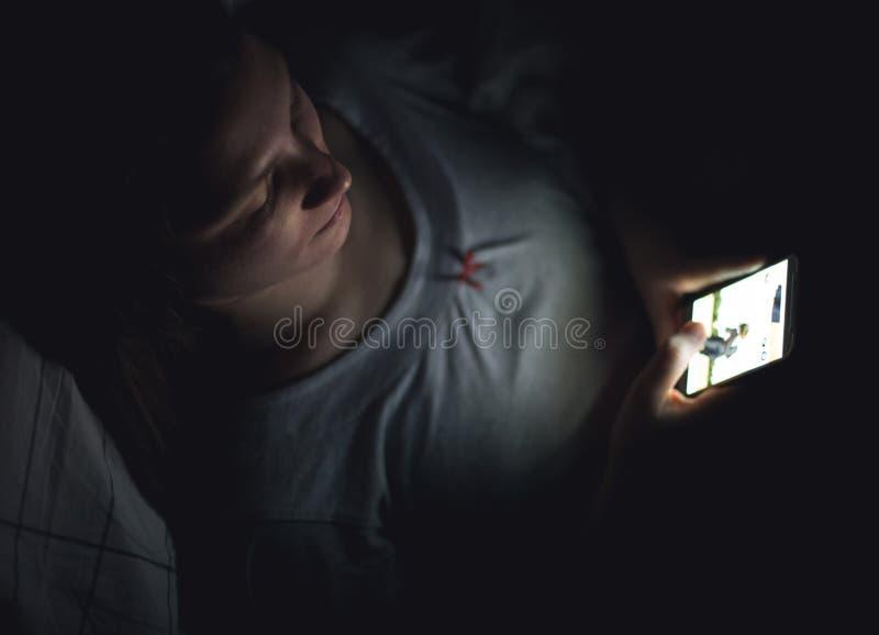 Mujer que usa el teléfono móvil en la oscuridad en su cama fotografía de archivo libre de regalías