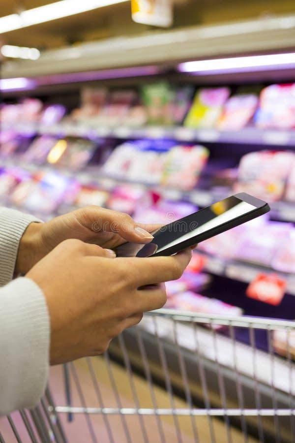 Mujer que usa el teléfono móvil mientras que hace compras en supermercado