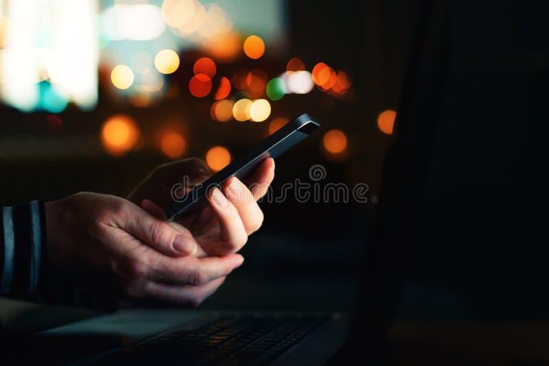 Mujer que usa el teléfono móvil para el envío de mensajes de texto en oscuridad fotos de archivo libres de regalías