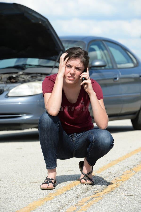 Mujer que usa el teléfono móvil para pedir ayuda del camino imagen de archivo