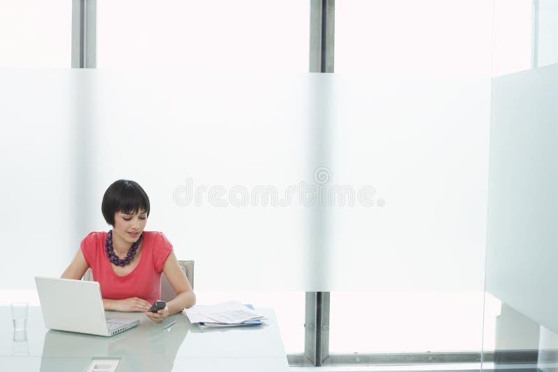 Mujer que usa el teléfono móvil y el ordenador portátil en cubículo moderno imagen de archivo libre de regalías
