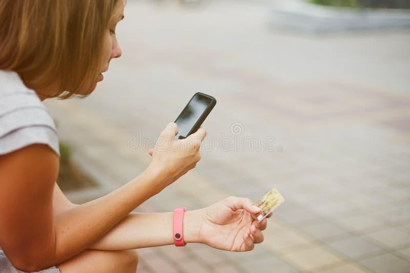 Mujer que usa el teléfono y la tarjeta para hacer compras fotos de archivo