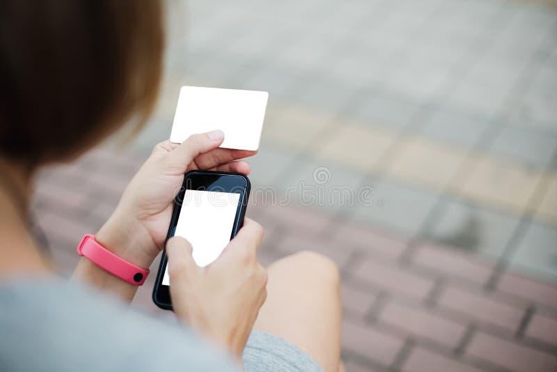 Mujer que usa el teléfono y la tarjeta para hacer compras fotografía de archivo libre de regalías
