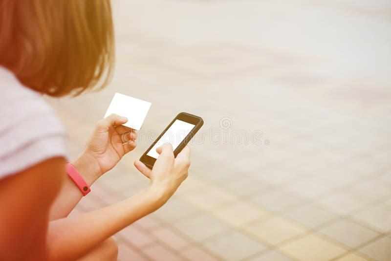 Mujer que usa el teléfono y la tarjeta para hacer compras imagenes de archivo