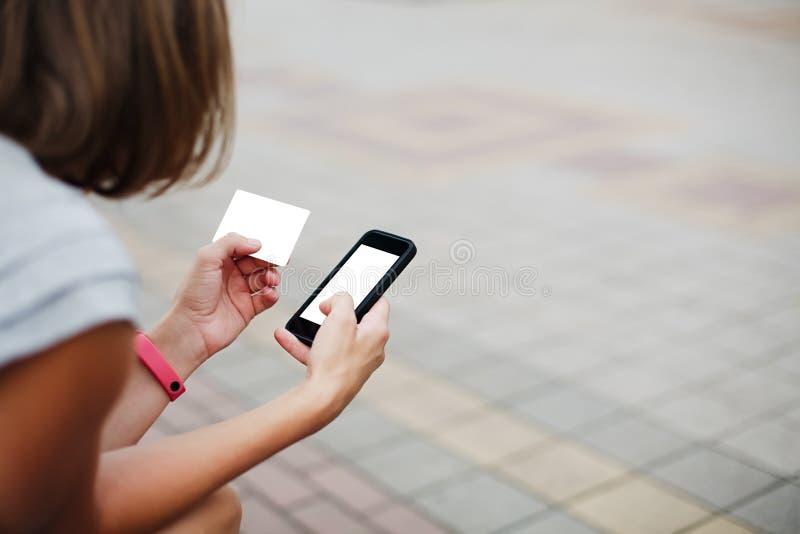 Mujer que usa el teléfono y la tarjeta para hacer compras fotos de archivo libres de regalías