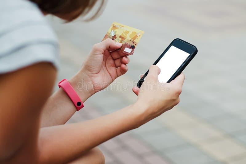 Mujer que usa el teléfono y la tarjeta para hacer compras foto de archivo libre de regalías