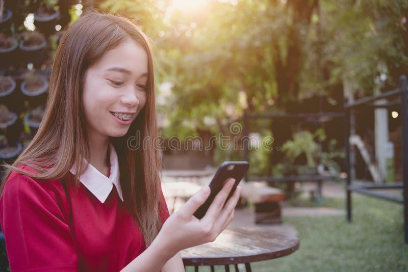 Mujer que usa el tel?fono m?vil mientras que soporte en el parque imagenes de archivo