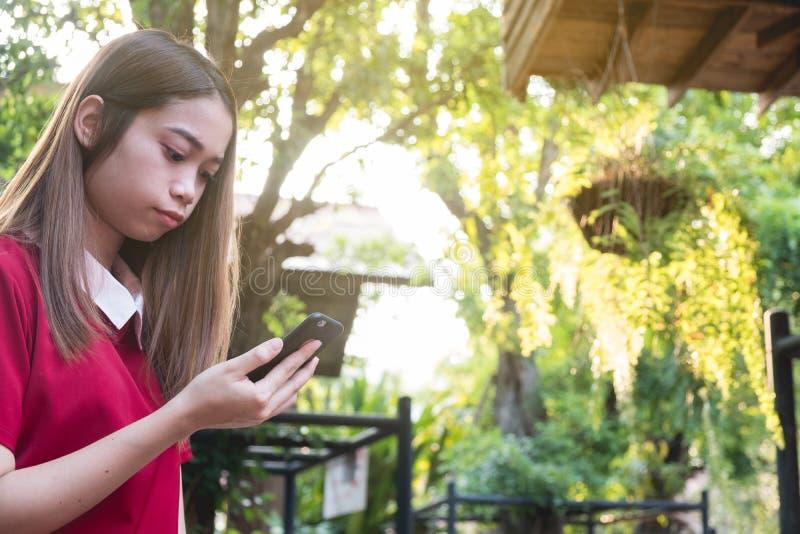 Mujer que usa el tel?fono m?vil mientras que soporte en el parque imágenes de archivo libres de regalías