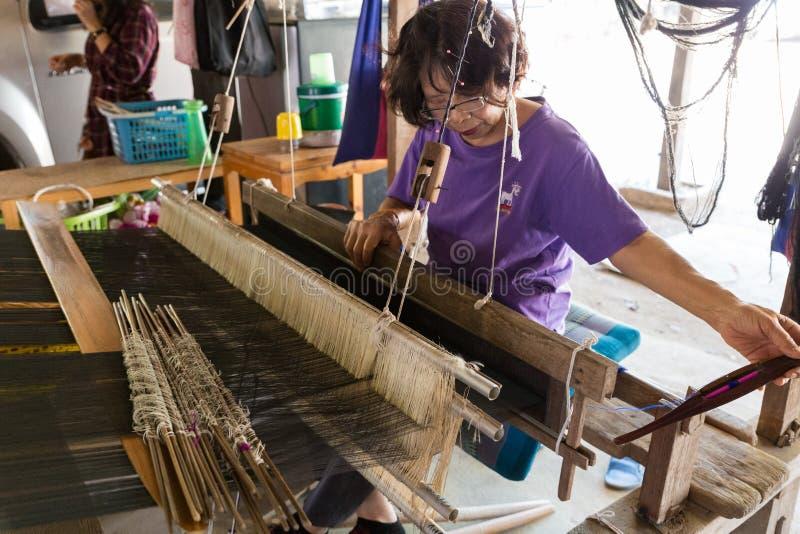 Mujer que usa el telar tradicional para tejer la materia textil de Tailandia fotografía de archivo libre de regalías