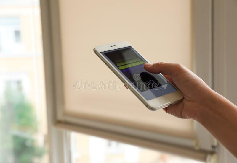 Mujer que usa el uso casero elegante en el teléfono a las persianas de ventana de control dentro Espacio para el texto imágenes de archivo libres de regalías