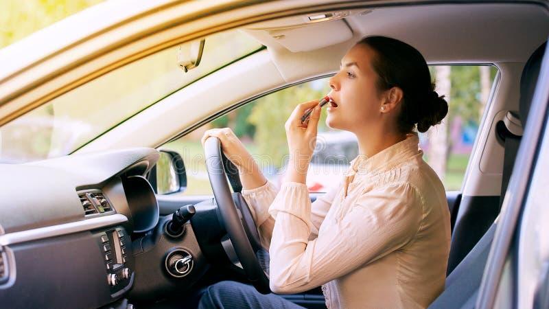 Mujer que usa la barra de labios dentro del coche Antecedentes urbanos Mún ocupado imágenes de archivo libres de regalías