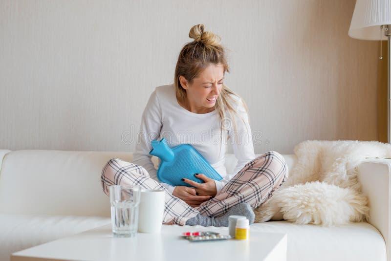 Mujer que usa la botella de agua caliente imagen de archivo