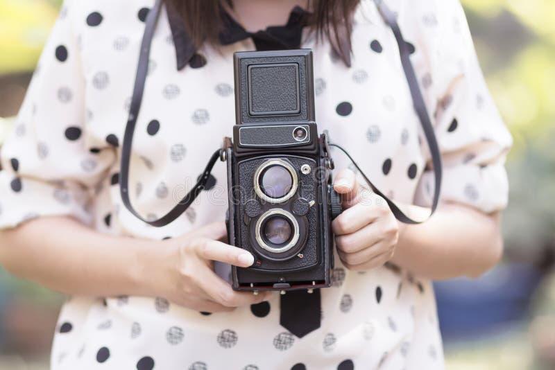 Mujer que usa la cámara de la vendimia imagen de archivo