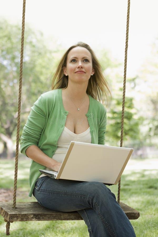 Mujer que usa la computadora portátil en un oscilación imágenes de archivo libres de regalías