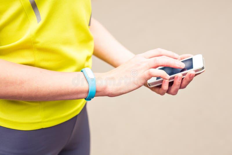 Mujer que usa la pulsera de la aptitud durante funcionamiento de la mañana foto de archivo