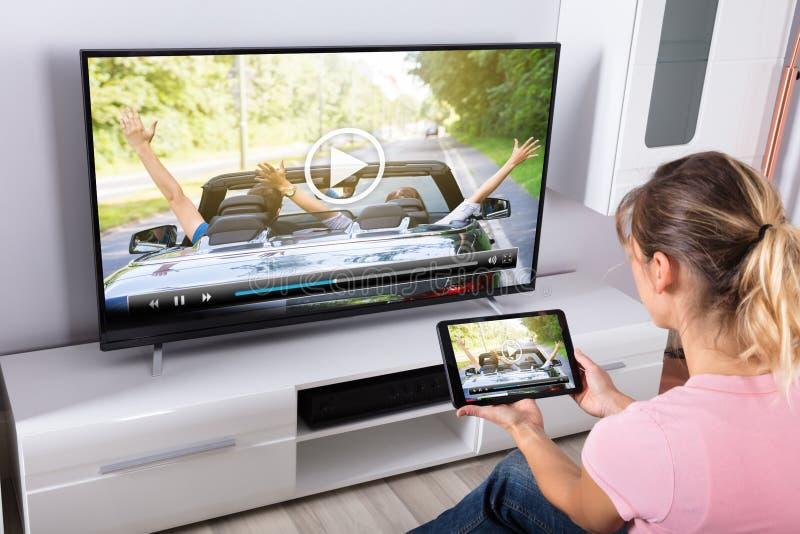Mujer que usa la tableta de Digitaces a la televisión de observación foto de archivo libre de regalías