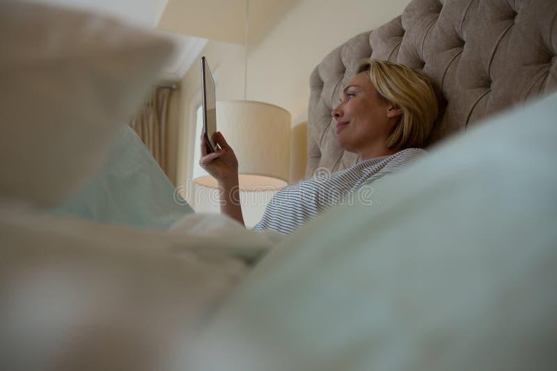 Mujer que usa la tableta digital mientras que se relaja en cama fotografía de archivo