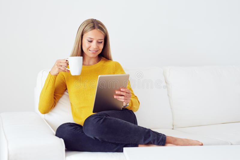 Mujer que usa la tableta que se sienta en el sofá foto de archivo