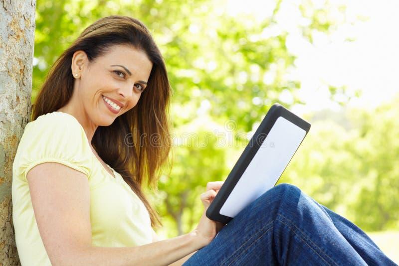 Mujer que usa la tablilla al aire libre fotos de archivo