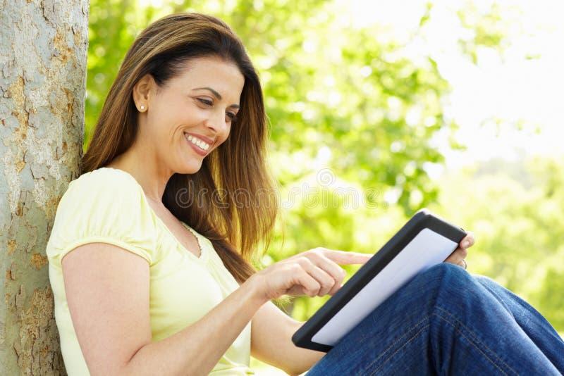 Mujer que usa la tablilla al aire libre fotografía de archivo