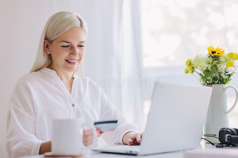 Mujer que usa la tarjeta de crédito para pagar en línea imagen de archivo libre de regalías