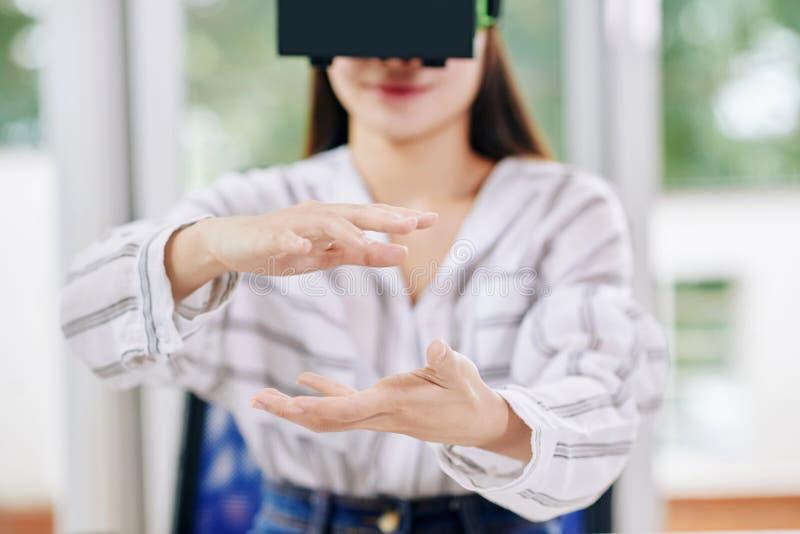Mujer que usa las auriculares de VR en el trabajo imagenes de archivo
