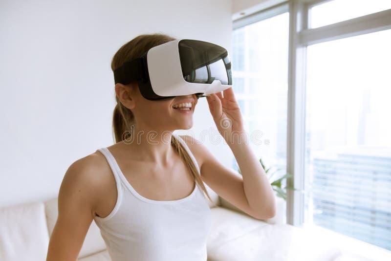 Mujer que usa los vidrios de la realidad virtual en casa imagenes de archivo