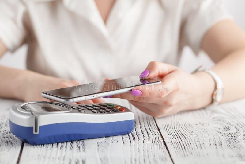Mujer que usa paga del teléfono móvil por NFC fotos de archivo libres de regalías
