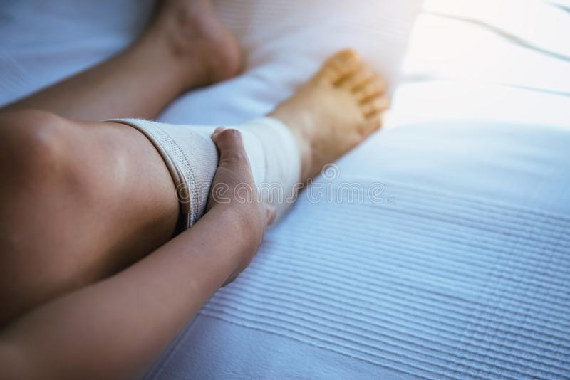 Mujer que usa puesto el vendaje elástico con las piernas que tienen dolor de la rodilla o de pierna imagen de archivo