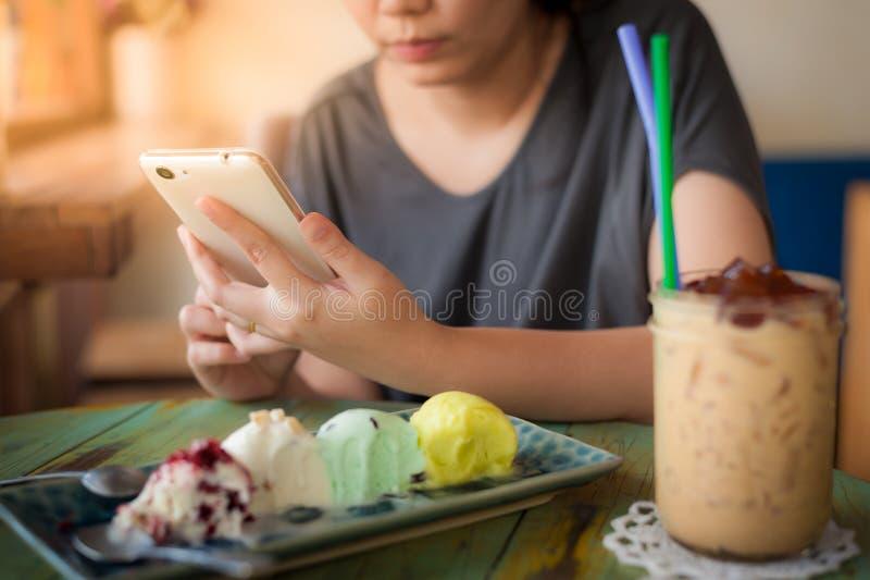 Mujer que usa smartphone en café foto de archivo