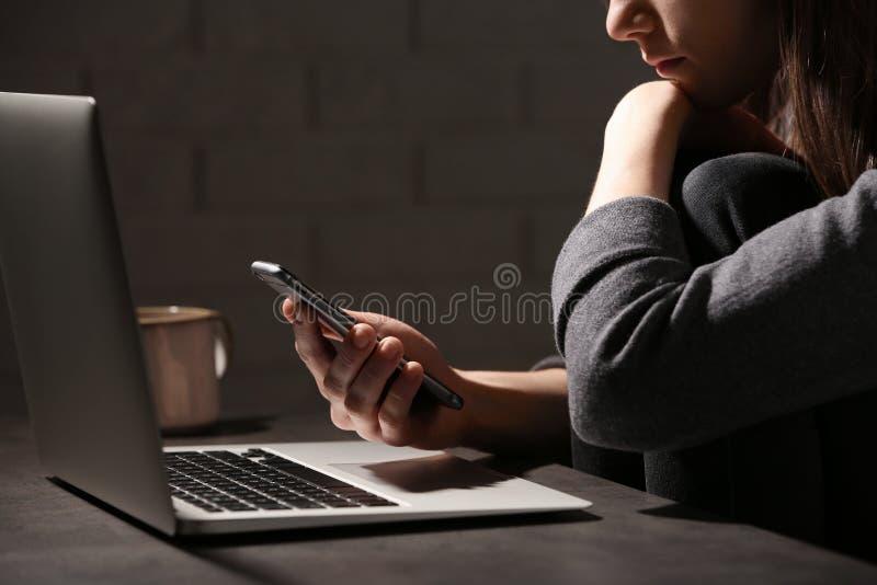 Mujer que usa smartphone en la tabla con el ordenador portátil en sitio oscuro Concepto de la soledad imagen de archivo libre de regalías