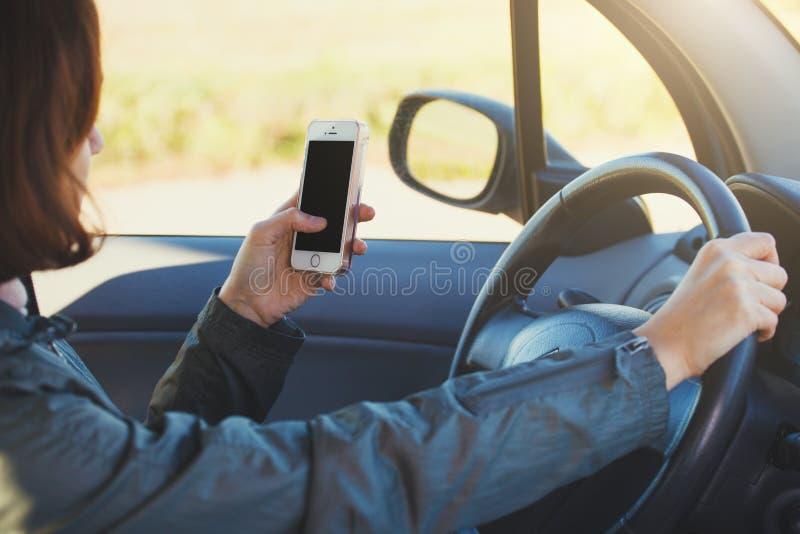 Mujer que usa smartphone mientras que conduce un coche imagen de archivo libre de regalías