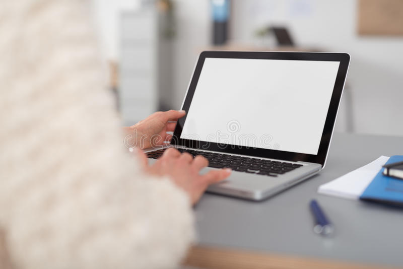 Mujer que usa su ordenador portátil con la pantalla blanca en blanco imagen de archivo