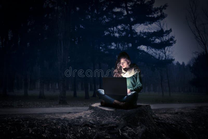Mujer que usa su ordenador portátil en la noche imagen de archivo